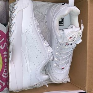 A pair of white fila shoes